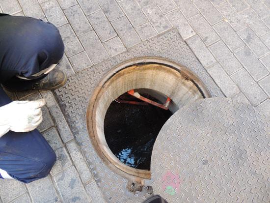 Operarios del Ayuntamiento de Huelva abren una alcantarilla.