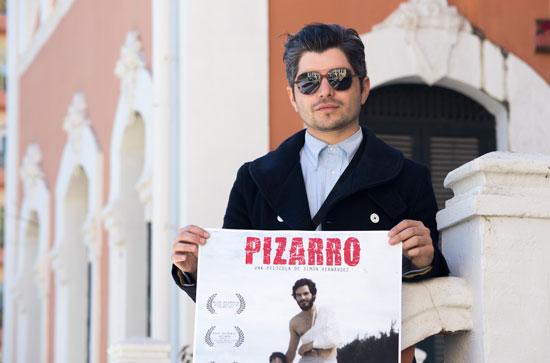 """Simón Hernández posa con el cartel de la película """"Pizarro""""."""