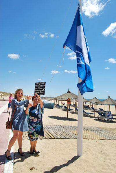 Grao y Márquez izan la bandera en la Playa Central.