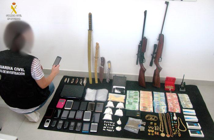 Un agente del Área de Investigación de la Guardia Civil muestra el material y la droga incautada.