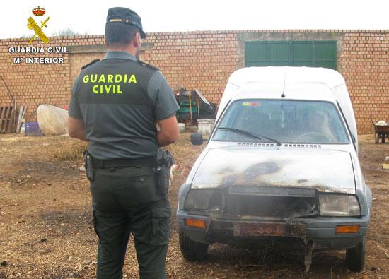 Un agente observa uno de los vehículos incendiados intencionadamente.