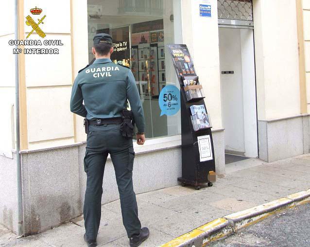 Imagen de un agente de la Guardia Civil delante de una tienda de telefonía de La Palma del Condado.
