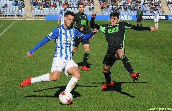 José Carlos Lazo ante la oposición de un jugador del Granada B.