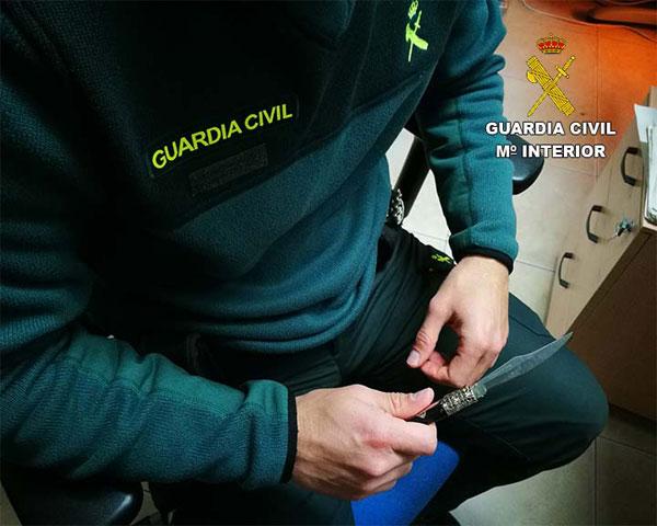 Un agente de la Guardia Civil sujeta el arma blanca intervenida.