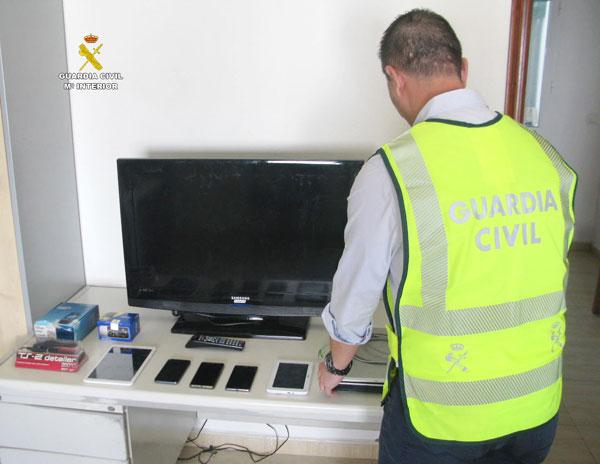 Un agente muestra algunos de los objetos intervenidos en la operación.