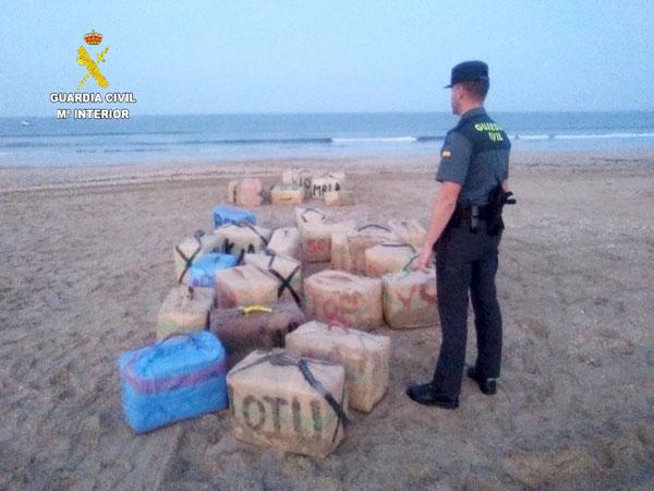 Un agente custodia los fardos en la playa.