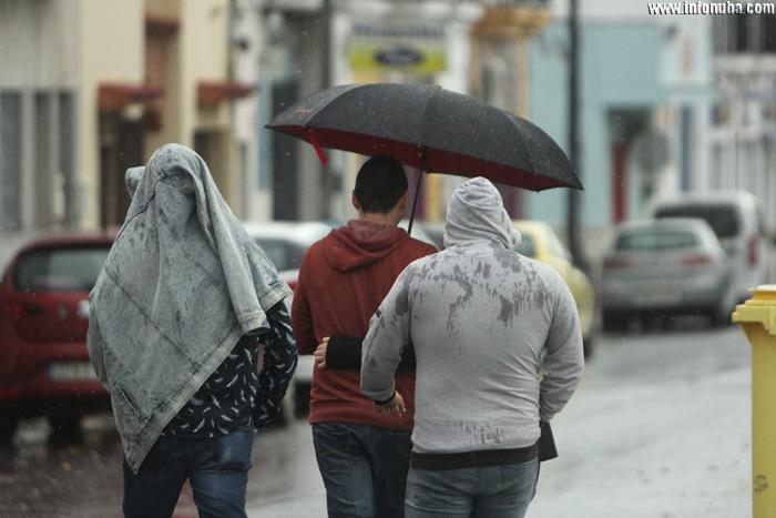 Personas se protegen de la lluvia.