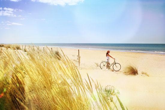 Una persona disfruta con su bicicleta en una de las playas onubenses.