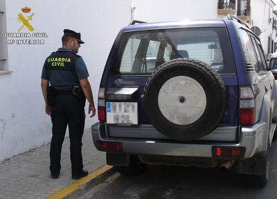 Un agente de la Guardia Civil observa el vehículo sustraído.