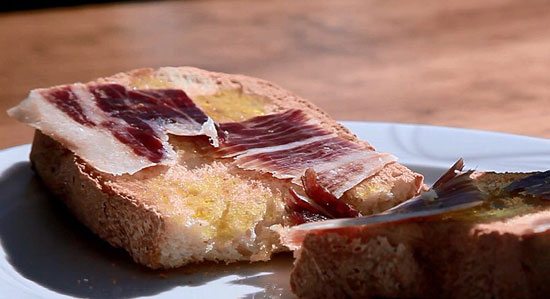 Imagen de una tostada con jamón y aceite.