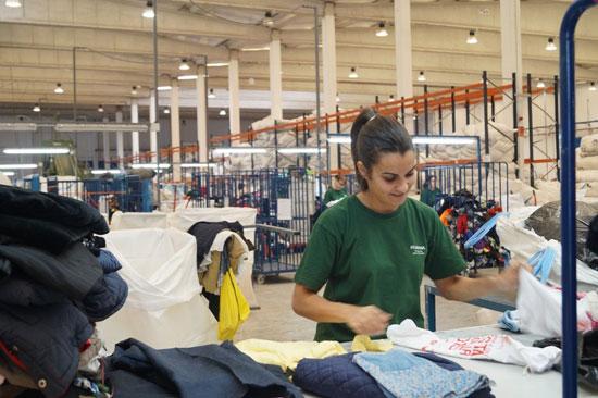 Una persona seleciona la ropa donada para su segundo uso.