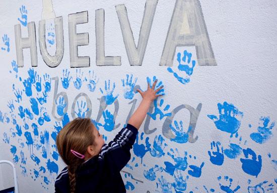 Una niña participando en la elaboración del mural.