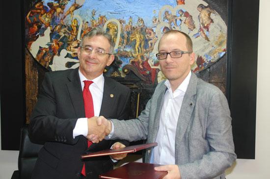 Francisco Ruiz y Manuel H. Martín estrechan sus manos tras la firma del convenio.