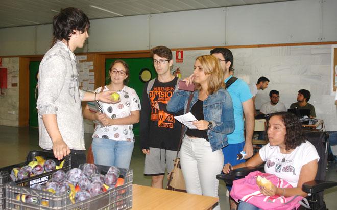 Un alumno ofrece una pieza de fruta a otros estudiantes.