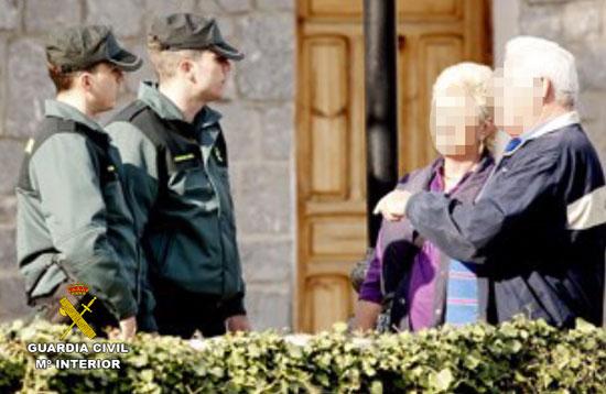 Dos agentes de la Guardia Civil dialogan con dos personas mayores.