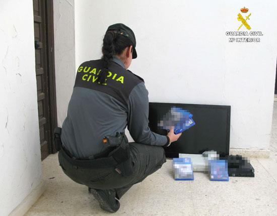 Una agente de la Guardia Civil muestra el material sustraído.