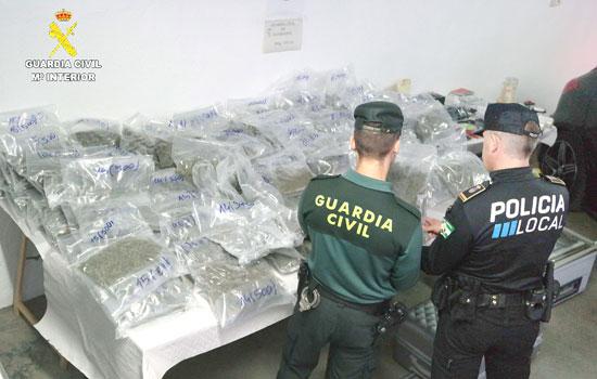 Dos agentes durante la exposición de la droga incautada.