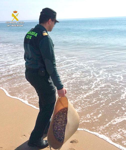 Un agente devuelve las coquinas al mar.