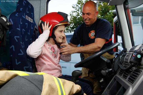 Un bombero de Cepsa ayuda a una niña a colocarse un casco de protección, durante una de las visitas enmarcadas en las Jornadas de Puertas Abiertas que la Compañía ofrece a la ciudadanía.